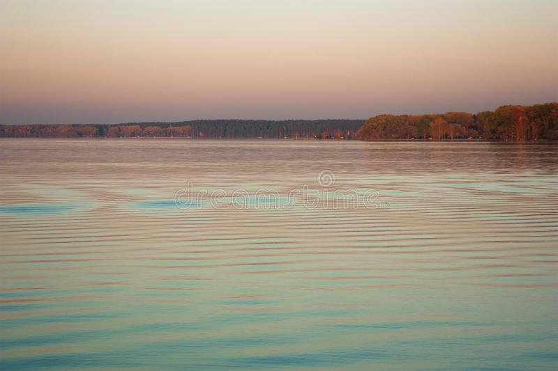 Beautiful lake landscape, and sunset. Blue waves and horizon line on water. Beautiful background. With red and green trees. Place for text on natural background royalty free stock images