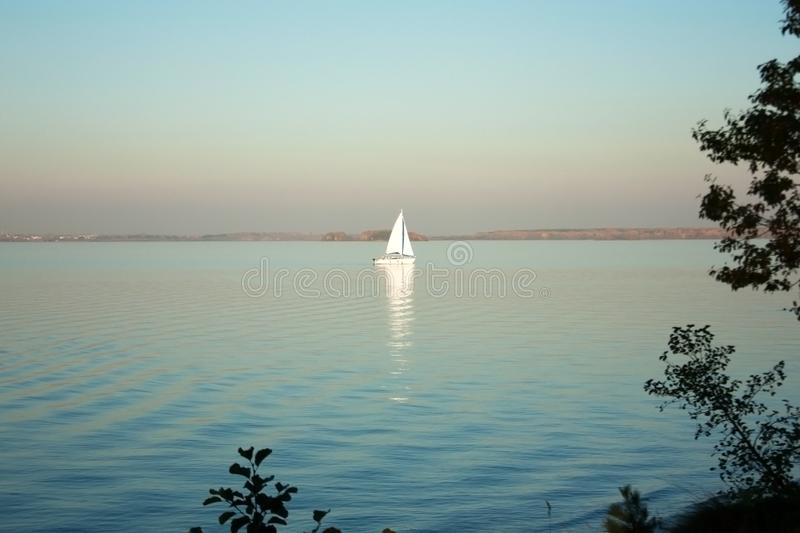 Beautiful lake landscape, yacht, and sunset. Blue waves, boat and horizon line on water. Beautiful background. With red and green trees. Place for text on stock photos