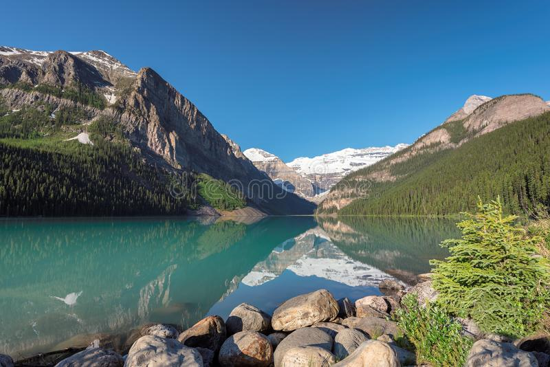 Beautiful Lake Louise in Rocky Mountains, Canada. Beautiful turquoise waters of the Lake Louise with snow-covered peaks above it in Rocky Mountains, Banff royalty free stock photos