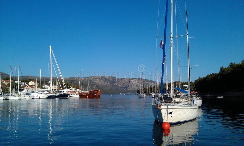 Beautiful lake with sailboats. Tranquil scene with sailing boats, some on mooring buoys stock photography