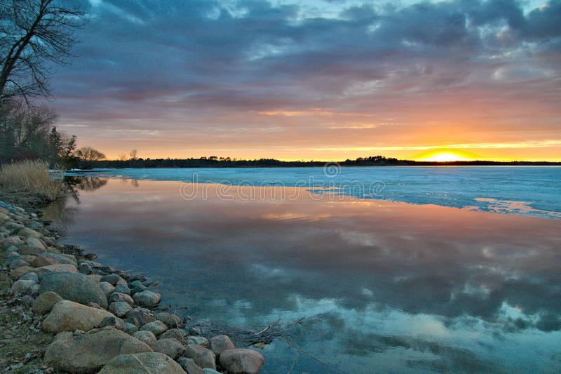 Beautiful lake shore in Minnesota at sunset with open water and ice stock image