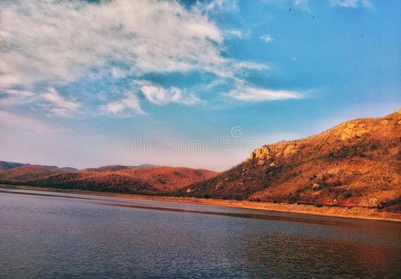 A beautfiul nature picture of lake, small hills and blue sky royalty free stock image