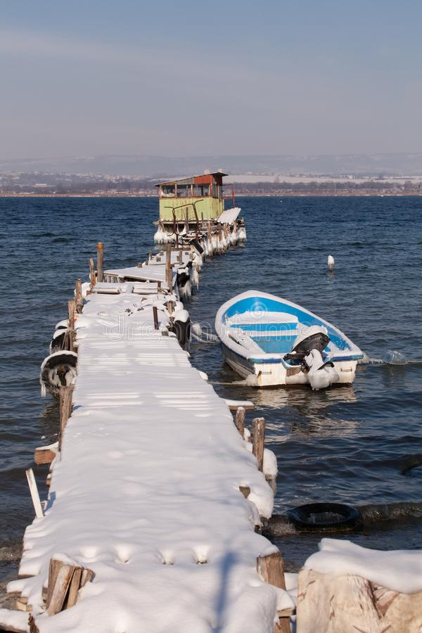 Beautiful lake winter scene with an old wooden pier and a fishing boat. The boat in snow at the lake in the winter stock photos