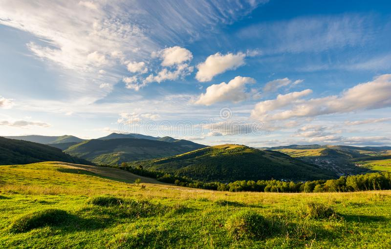 Beautiful landscape in afternoon. Gorgeous blue sky with golden clouds over the mighty mountain ridge in the distance. magical moment of nature royalty free stock photos