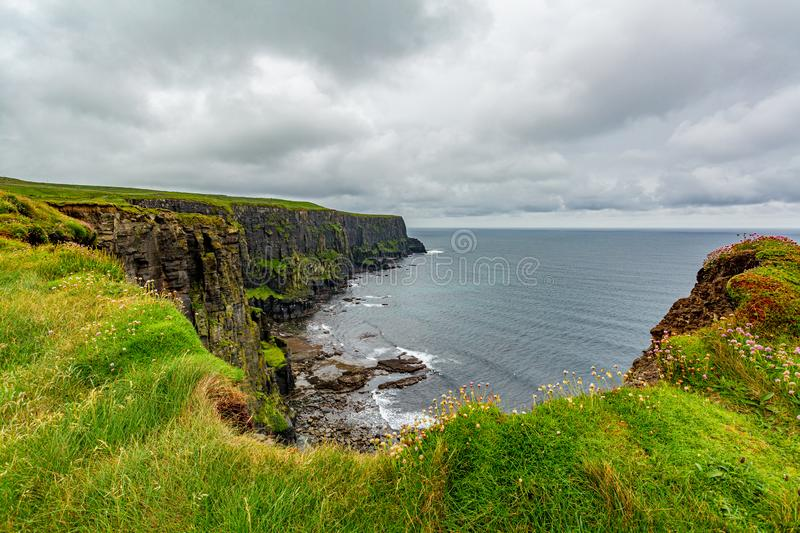 Beautiful landscape along the coastal walk route from Doolin to the Cliffs of Moher. Geosites and geopark, Wild Atlantic Way, spring rainy day in the stock image