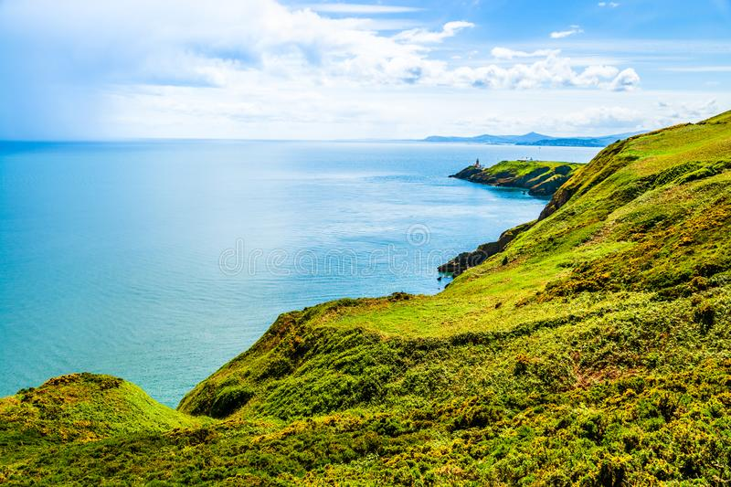 Beautiful landscape of the Atlantic Ocean shoreline and lighthouse. Clifftop trail on hills  covered in gorse yellow flowers on stock image