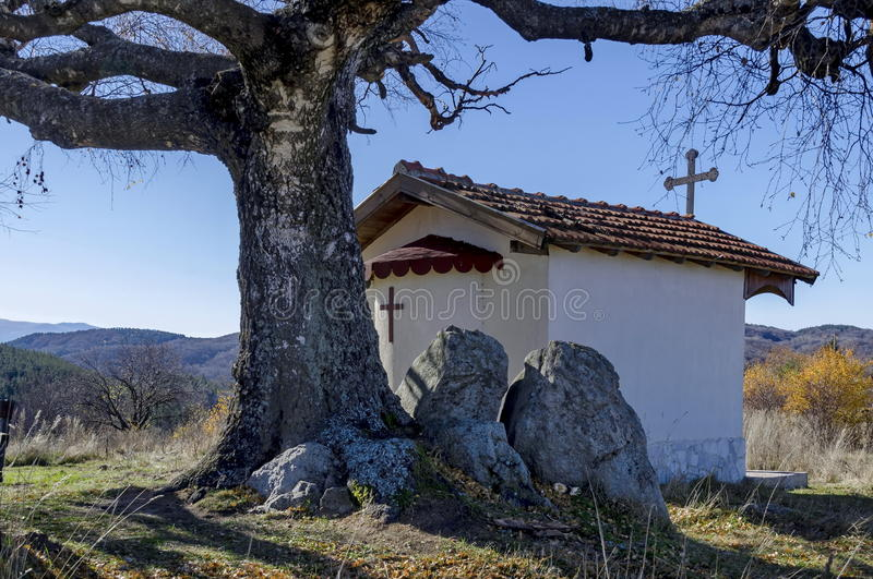 Beautiful landscape with autumnal venerable birch tree and old chapel, located in Plana mountain, Bulgaria stock photo
