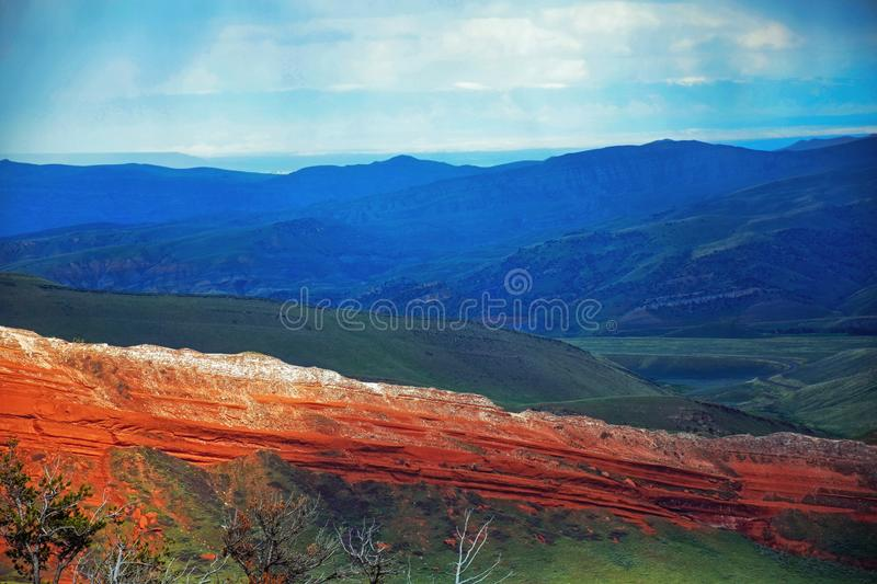 Glowing red rocks on Highway 296 near Cody, Wyoming. A beautiful landscape with blue mountains, green meadow, and glowing red or orange rocks on Chief Joseph royalty free stock image