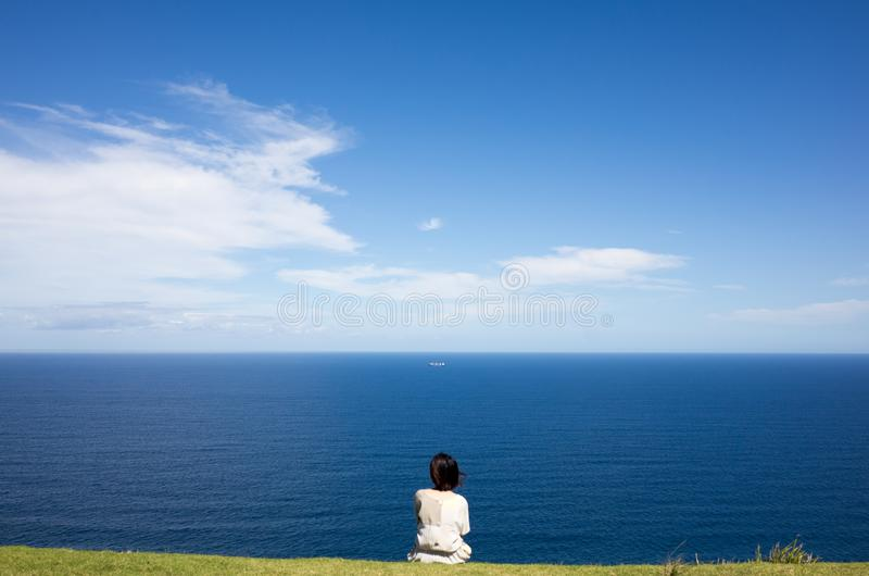 Beautiful landscape of blue ocean and sky, a girl sitting stock photos