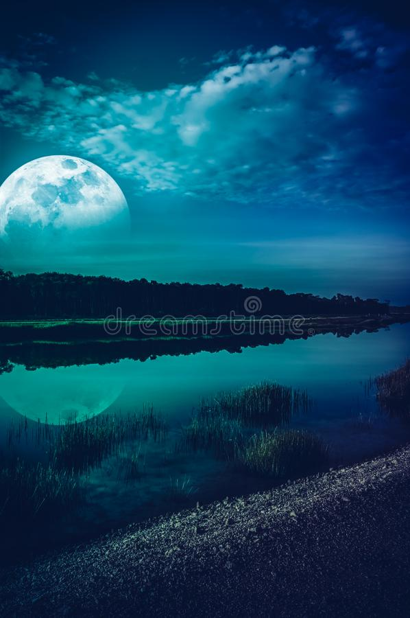 Beautiful landscape of blue sky with cloud and super moon above silhouettes of trees at riverside. Serenity nature background,. Outdoor at nighttime. The moon stock photo