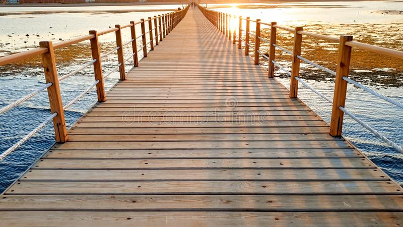 Beautiful landscape of calm ocean waves and long wooden pier. Amazing jetty at sea aagainst sunset over the mountains. Beautiful landscape of calm ocean waves stock photo