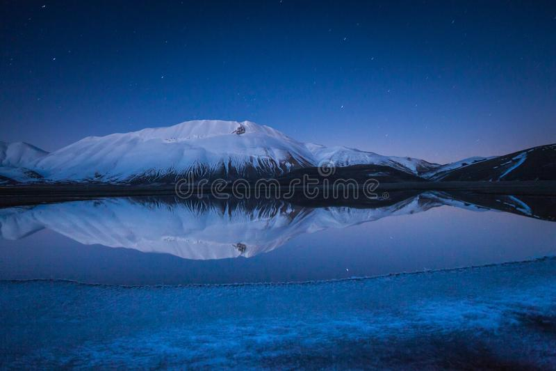 Beautiful landscape in Castelluccio di Norcia during a frozen night on Mount Redentore reflected in the lake, Umbria, Italy royalty free stock photo