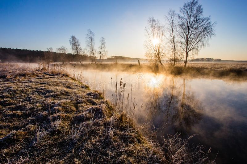 Beautiful landscape. Climate concept. Bright sun rises on cold frosty morning. Fog above river. Beautiful landscape. Climate concept. Bright sun rises on a cold stock photo