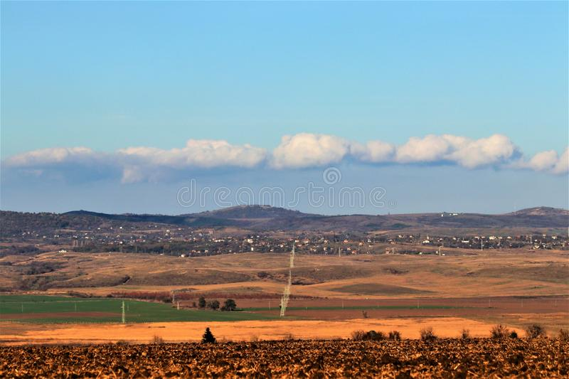 Beautiful landscape in contrasting colors, blue sky in white. Beautiful landscape in contrasting colors, field, green grass, soil, mountains and beautiful blue royalty free stock images