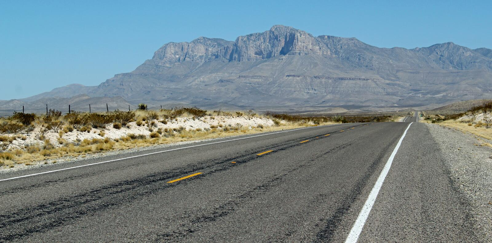 On the road again: Highway in the USA / Texas. Long straight road across unbelievable wide landscape. Beautiful landscape / distinctive mountains and dry deserts stock image