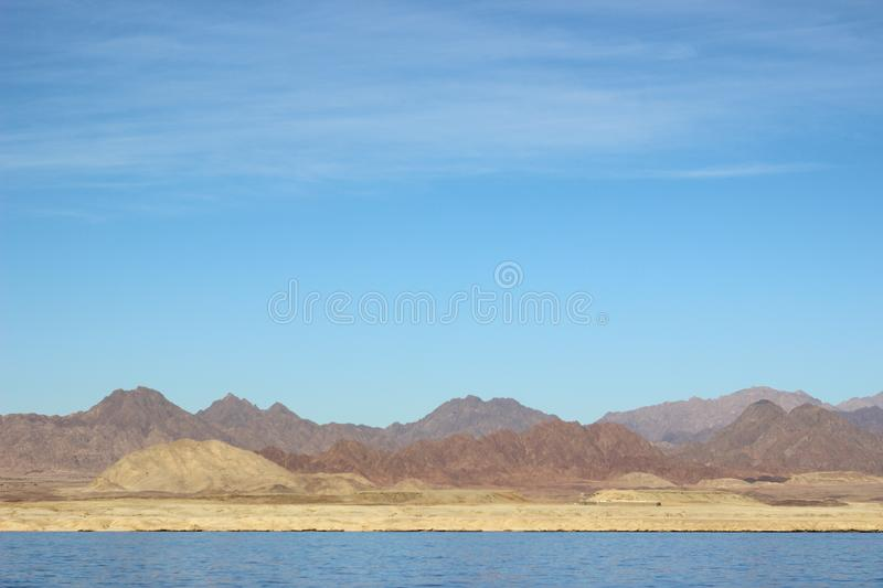 Beautiful landscape. Egyptian mountains and the red sea. Light clouds in the blue sky. Energy of the desert, sky, mountains and sea royalty free stock image