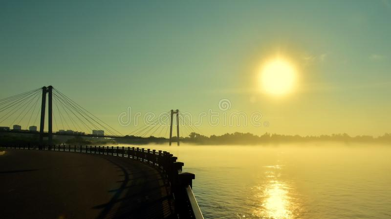 Beautiful landscape. Fog over the river at sunrise. Silhouette of a cable-stayed bridge. Reflection of the sun in water. royalty free stock images
