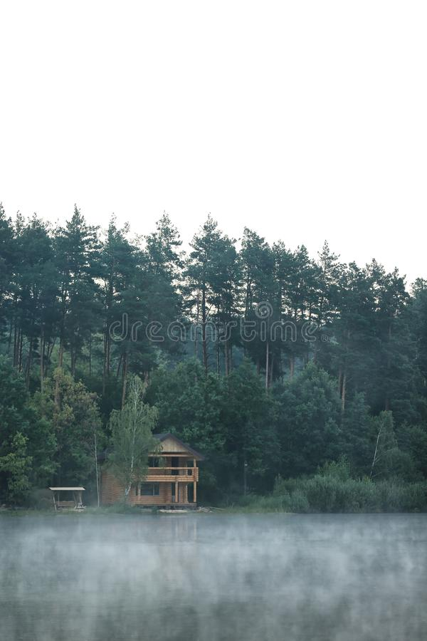 Beautiful landscape with forest and house near lake royalty free stock photo