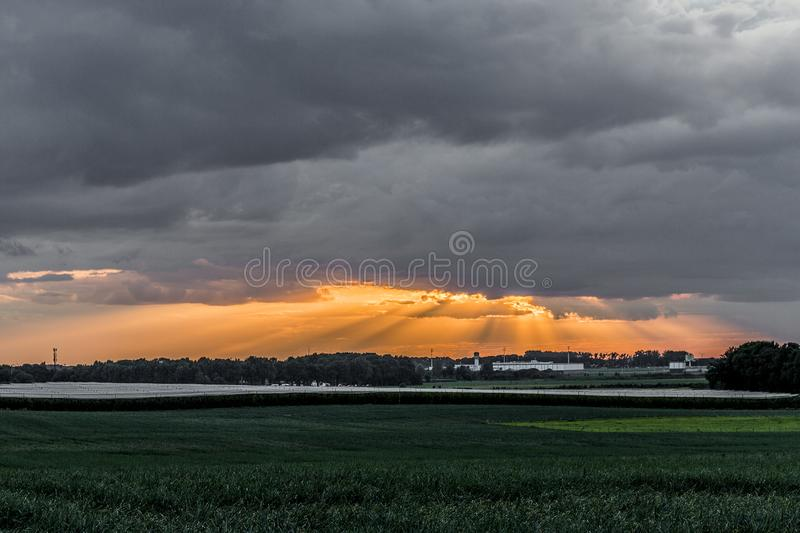 Beautiful landscape of a green field cultivated in a wonderful sunset with the rays of the sun rising through the clouds. Cloudy day in Beek, south Limburg in stock photo