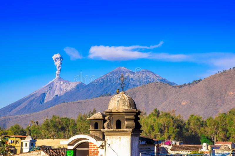 Beautiful landscape of huge mountain in process of aruption with a column of ash, view from the rooftops of the building. In Antigua city in gorgeous sunny day royalty free stock image