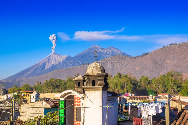 Beautiful landscape of huge mountain in process of aruption with a column of ash, view from the rooftops of the building. In Antigua city in gorgeous sunny day stock photos