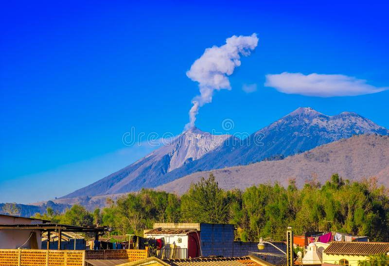 Beautiful landscape of huge mountain in process of aruption with a column of ash, view from the rooftops of the building. In Antigua city in gorgeous sunny day royalty free stock images