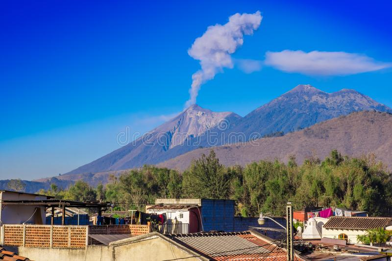 Beautiful landscape of huge mountain in process of aruption with a column of ash, view from the rooftops of the building. In Antigua city in gorgeous sunny day stock image