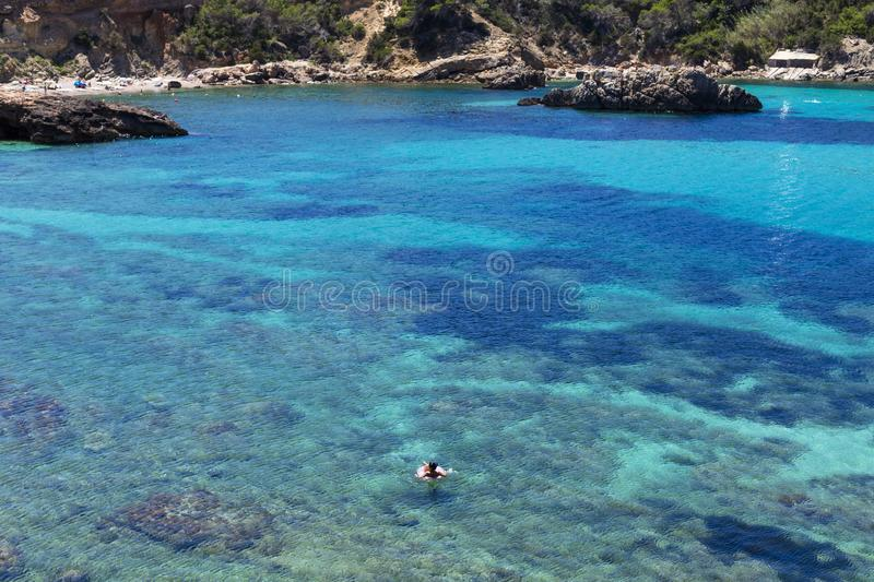 Beautiful landscape in Ibiza of blue ocean in a sunny day with a woman floating on a flatable donuts. Summer and holidays concept. Isle, water, scenic, spanish royalty free stock images