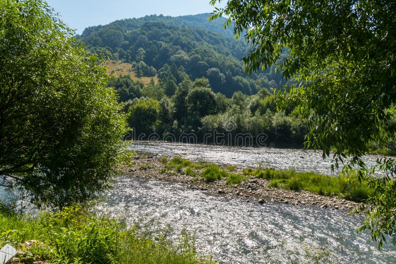 A beautiful landscape of mountainous terrain slopes covered with greenery, the river babbling leisurely on its business stock photo