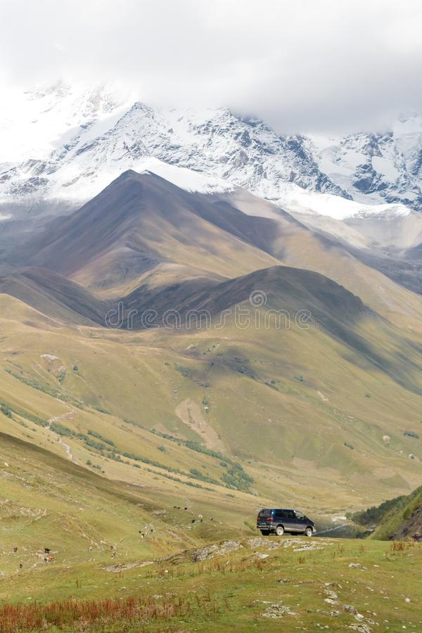 Beautiful landscape of mountains in Georgia, with staying car far away. Snow covered peaks background. royalty free stock photos