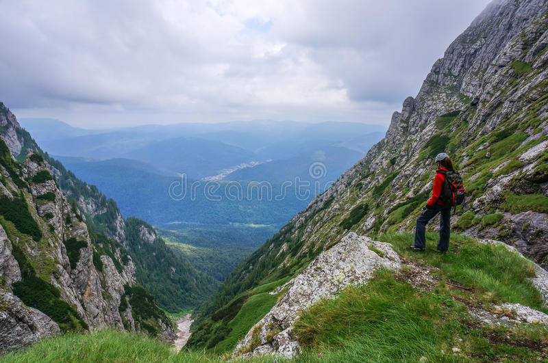 Beautiful landscape in the mountains and woman climber admiring the view stock image