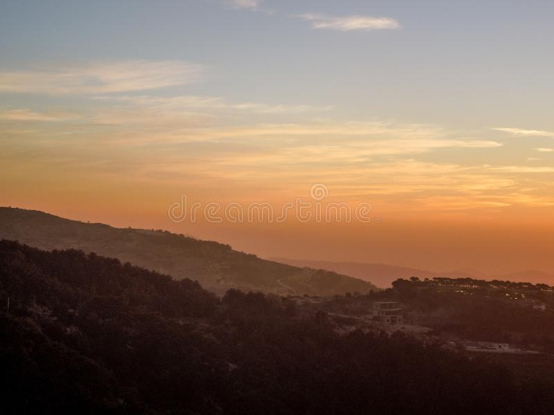 Beautiful landscape in Niha , the lebanese village with black mountains silhouettes and orange sky. Beautiful landscape in Niha , the lebanese village with black stock image