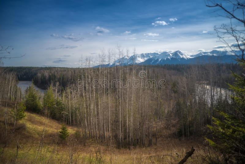 Mountains behind the River Bend. A beautiful landscape of northern Canada is depicted with mountains, forests, openings and a river bend, all under a blue spring royalty free stock photo
