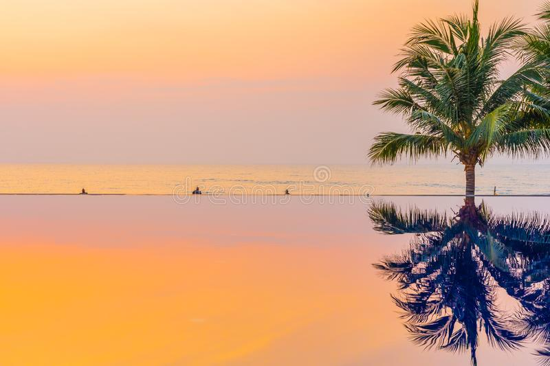 Beautiful landscape outdoor with coconut palm tree around swimming pool in hotel and resort at sunrise or sunset time. For leisure vacation and travel stock photo
