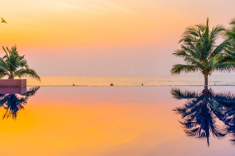 Beautiful landscape outdoor with coconut palm tree around swimming pool in hotel and resort at sunrise or sunset time. For leisure vacation and travel royalty free stock images