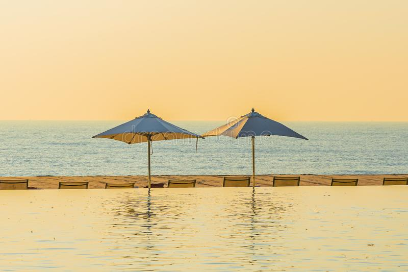 Beautiful landscape outdoor swimming pool with umbrella and deck chair in hotel resort for relax travel and vacation. At sunrise or sunset time royalty free stock images