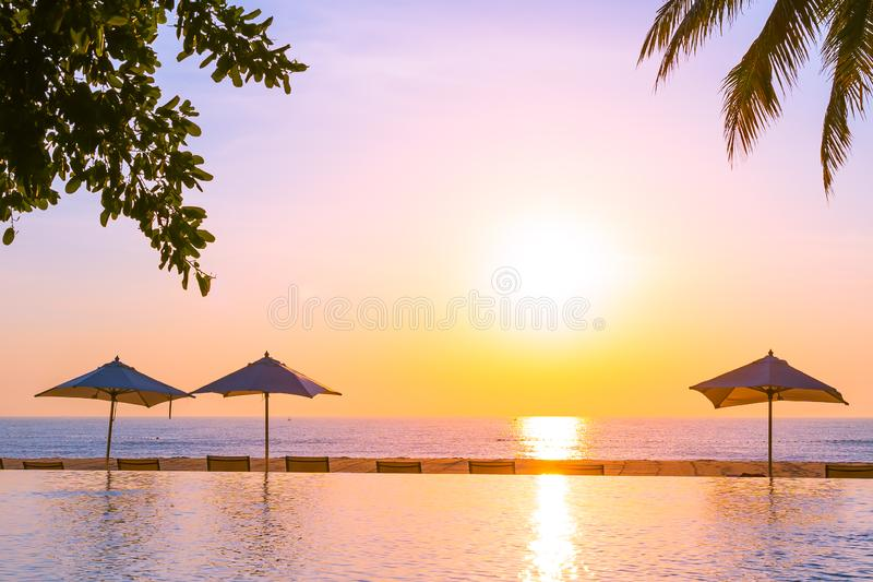 Beautiful landscape outdoor swimming pool with umbrella and deck chair in hotel resort for relax travel and vacation. At sunrise or sunset time royalty free stock photos