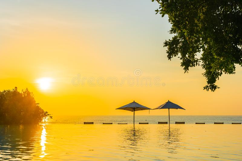 Beautiful landscape outdoor swimming pool with umbrella and deck chair in hotel resort for relax travel and vacation royalty free stock image