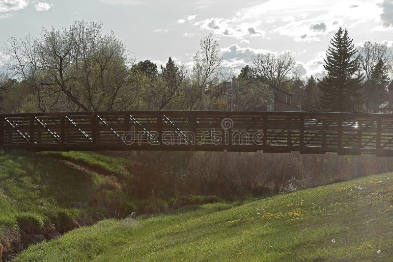 Beautiful landscape with pedestrian bridge in the small neighborhood park. Aurora, Colorado royalty free stock photos