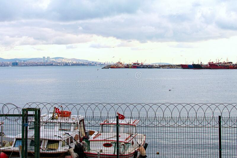 Beautiful landscape photo of harbor with moored fishing boats and ships in Istanbul. Cityscape in the background. Dramatic winter sky. Istanbul, Turkey royalty free stock images