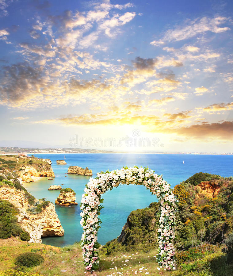 Beautiful landscape of portugal Rocky beach with wedding arch. Decorated with flowers of white roses at sunset. Wedding and honeymoon concept stock photos