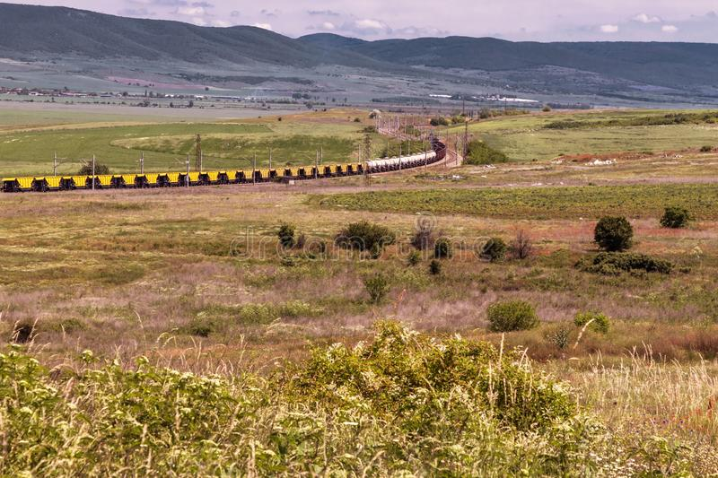 Beautiful landscape, railway train through the green field, high mountains stock images