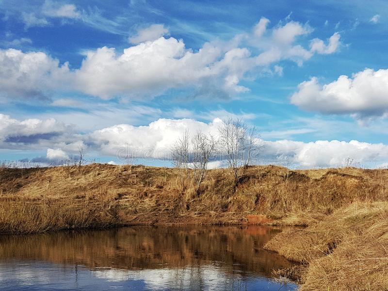 Beautiful landscape on the river bank and the blue sky with clouds stock images