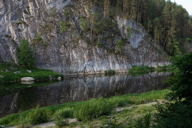 beautiful landscape, a rock is reflected in a mountain river, around the forest and green grass stock photo