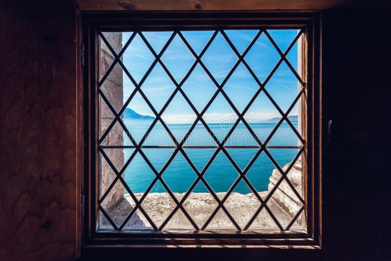 Beautiful Landscape Scenery View of Geneva Lake, Switzerland From inside of Chillon Castle. Tranquil Scenic View With Old Window. Frame at Montreux City of stock photo
