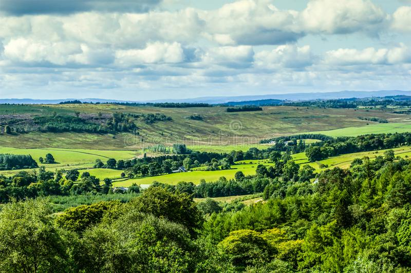 Beautiful landscape in Scotland with hills, fields and white clouds. In Summer stock image