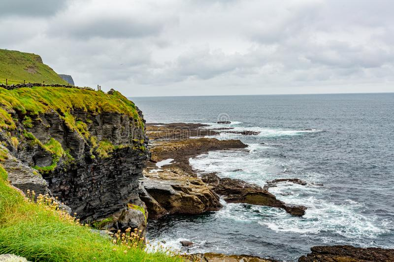 Beautiful landscape of the sea and limestone along the coastal walk route from Doolin to the Cliffs of Moher. Geosites and geopark, Wild Atlantic Way, rainy royalty free stock images