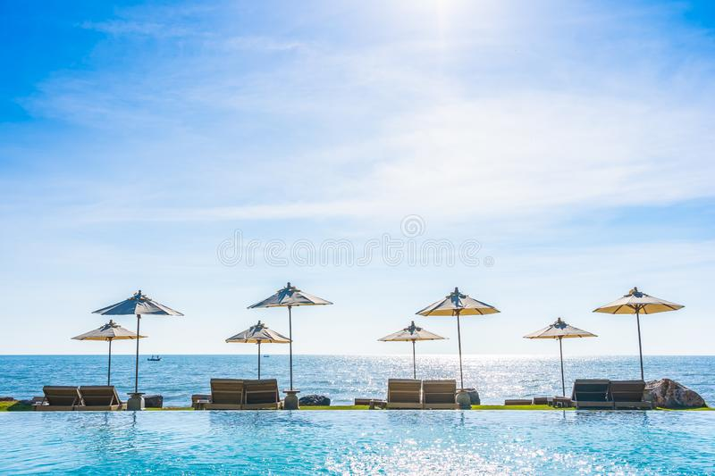 Beautiful landscape of sea ocean on sky with umbrella and chair around luxury outdoor swimming pool stock images