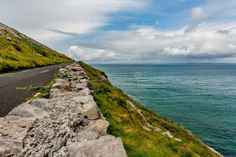 Beautiful landscape with the sea and the rural coastal R477 road along ​​the Burren. Geosite and geopark, Wild Atlantic Way, cloudy spring day in royalty free stock photos