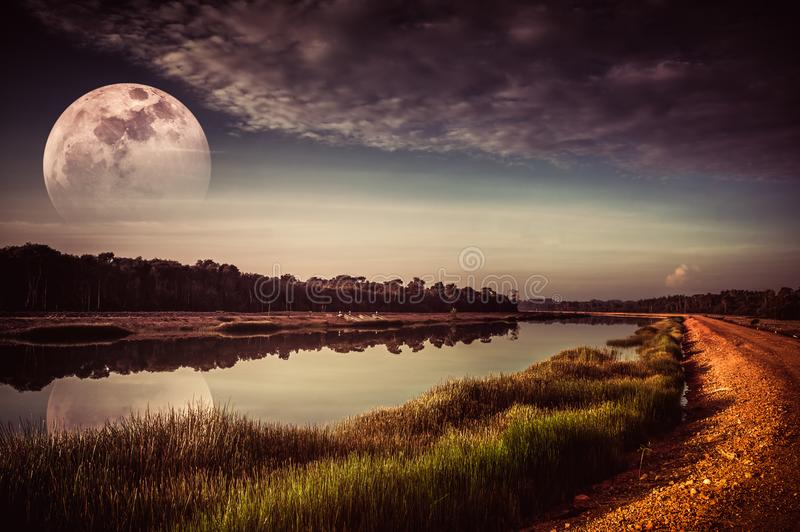 Night sky and super moon at riverside. Serenity nature backgroun. Beautiful landscape of sky with cloud and fade half super moon above silhouettes of trees at stock images